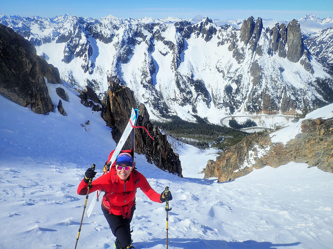 Natalie making her way up a snowy chute with skis on her back using the help of Trail Three poles.