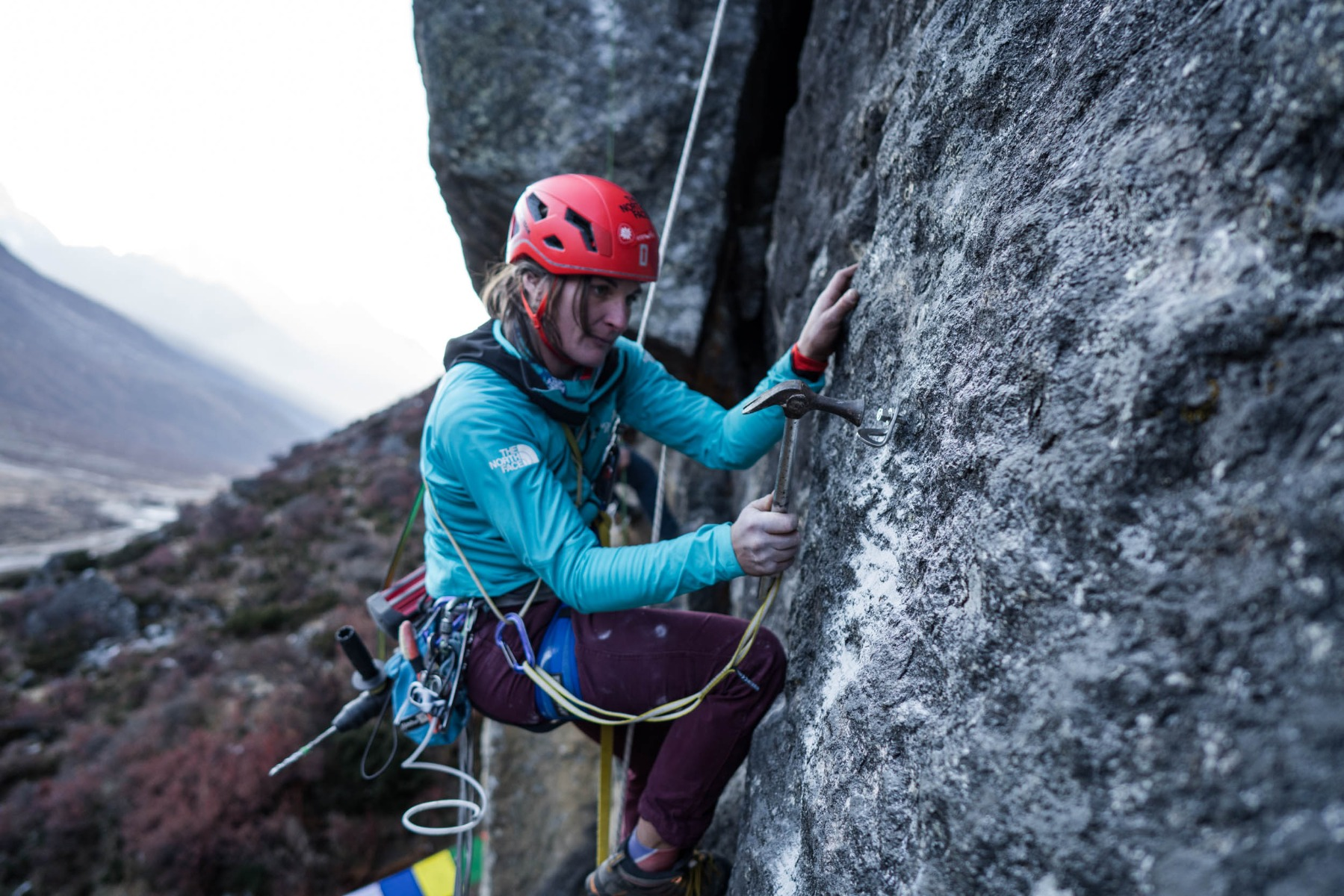 Josie hammering a bolt into the rock.
