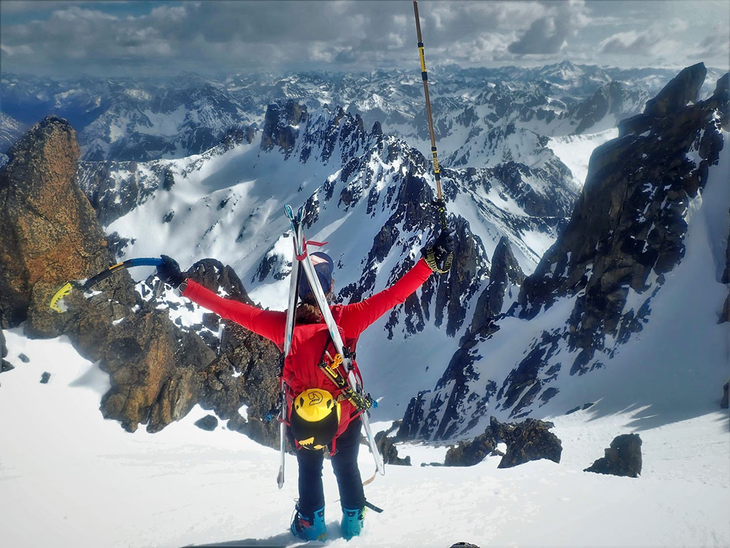 Natalie atop a mountain holding up both arms in victory. A Grivel ice axe is in one hand a a grivel pole in the other.